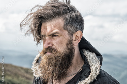 hipster, bearded man on mountain top on natural cloudy sky Fototapete