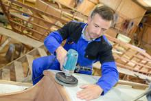 Craftsman Sanding Wooden Boat Structure