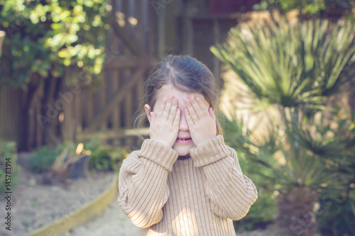 Fotografia, Obraz  Little girl playing hide and seek in the garden, holding her hands in front of h
