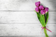 Beautiful bouquet of lilac tulips on light wooden background
