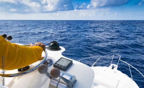 Fotografía  Hand of captain on steering wheel of motor boat in the blue ocean