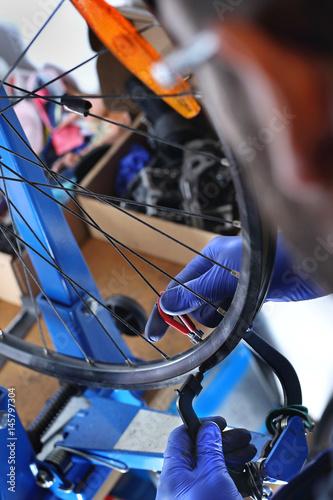 Obraz Serwis rowerowy naprawa koła. Mechanik w serwisie rowerowym naprawia koło w rowerze.  - fototapety do salonu