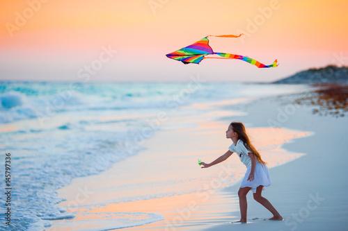 Little running girl with flying kite on tropical beach at sunset Wallpaper Mural