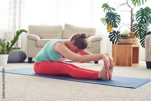 Fototapeta Gorgeous chestnut practicing yoga in seated forward bend obraz na płótnie