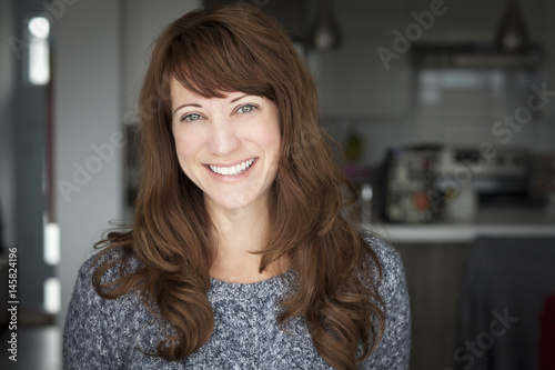Photographie  Portrait Of A Mature woman smiling At The Camera. In the kitchen.