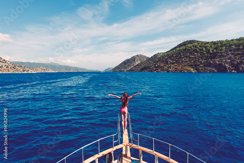 Girl dives or jumps with a long jump from the boat into the open sea in a landscape with mountains Wallpaper Mural