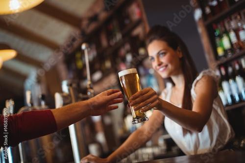 Female bar tender giving glass of beer to customer
