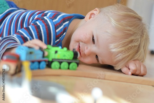 Fotografie, Obraz  Smiling boy playing with a locomotives