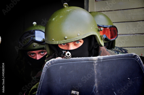 Photo  The military man in a helmet and wearing a mask holds a shield and a gun in his