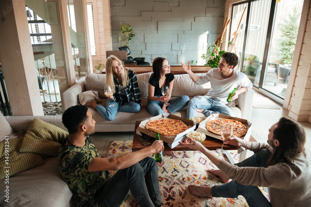 Fototapety, obrazy: Group of young cheerful friends hanging out together at home