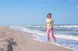 Joyful sporty woman, with flying hair, is expressively laughing on the beach