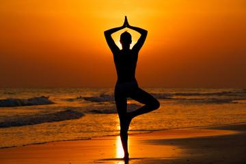 Kobieta ćwicząca jogę na plaży przy zachodzie słońca