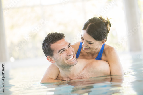 Cheerful couple in a swimming pool Canvas-taulu