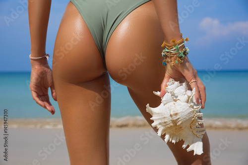 Fotografie, Obraz  Sporty back of a beautiful woman in bikini with a seashell in her hands on sea background