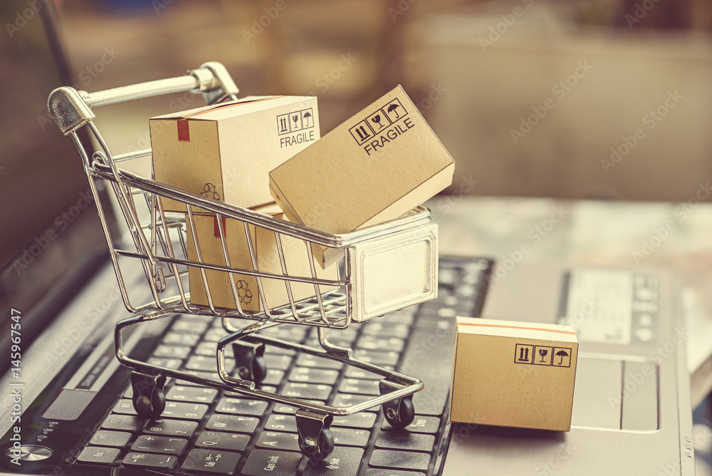 Fototapeta Paper boxes in a shopping cart on a laptop keyboard. Ideas about e-commerce, e-commerce or electronic commerce is a transaction of buying or selling goods or services online over the internet.