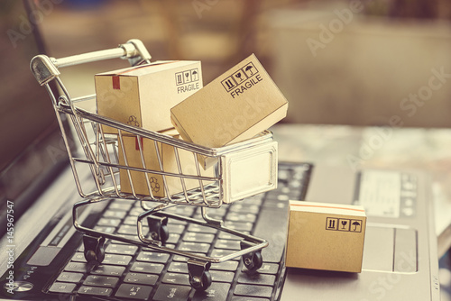 Valokuva  Paper boxes in a shopping cart on a laptop keyboard