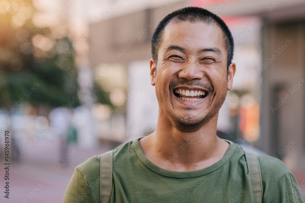 Fototapety, obrazy: Asian man laughing while standing on a city street