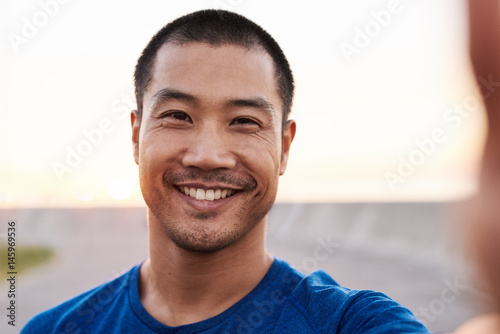 Obraz na plátne  Athletic Asian man taking a selfie during a morning run