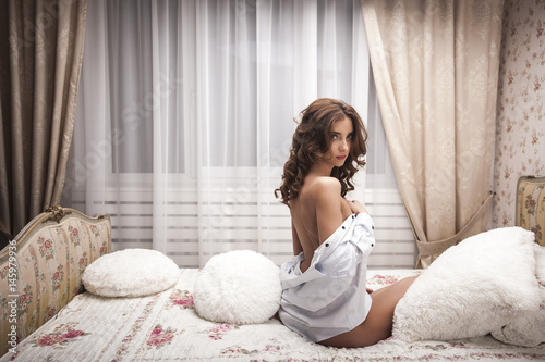 Beautiful sexy woman wearing seductive white lingerie and men shirt posing in be Canvas Print