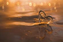 Clear Glass Heart On  Sand Beach With Sunrise Sun Light
