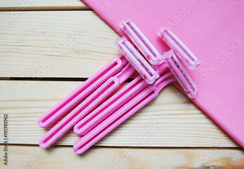 A bunch of women's disposable razors on wooden table.