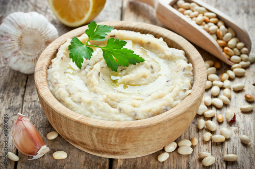 White beans hummus with lemon, garlic and flax in wooden bowl