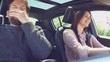 Man and woman in love joking in car driving towards vacation