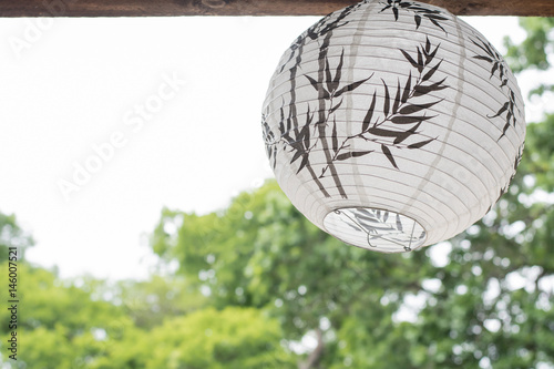 a white Japanese lantern hanging on the wooded roof  with green trees background Poster