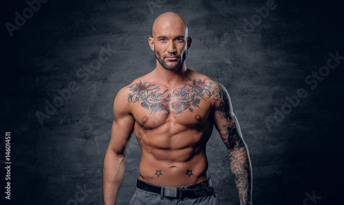 Fotografie, Tablou Shaved head, muscular male with tattoos on his torso over grey vignette background