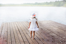 Cute Little Girl Standing On A Bridge, Looking At The Beautiful Lake. Foggy Air.