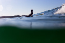 A Surfer Is Back Lit By The Ev...