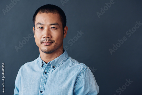 Fotografia  Confident and focused young Asian designer standing in an office