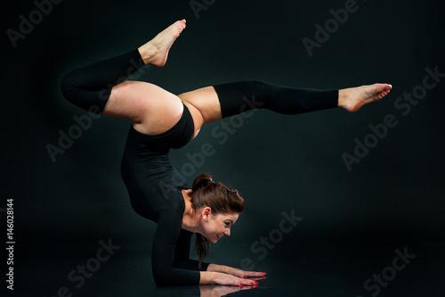 Foto auf Gartenposter Gymnastik Flexible gymnast doing exercise on black background Hands Standing Upside Down