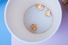 A Top View Of A Cup With The Remnants Of The Popcorn On The Bottom, Purple Background, Paper Cup,