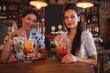 Portrait of two young women having cocktail drinks