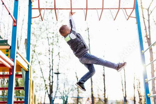 Fotografia  Little boy play on playground with blur park background