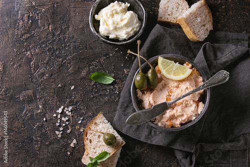 Poster de jardin Entree Black bowl of salmon pate with red caviar served with butter, sliced bread, capers, vintage knife and herbs on textile linen napkin over brown texture background. Top view.