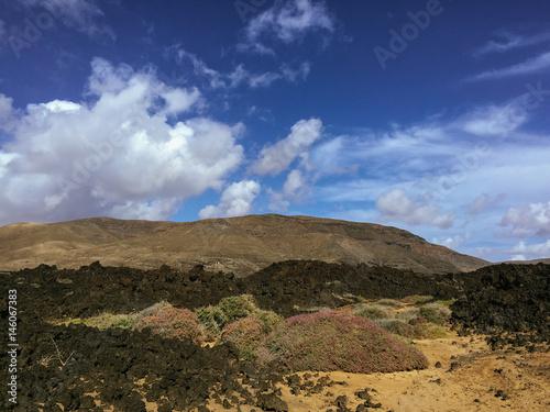 Tuinposter Canarische Eilanden Beautiful view overlooking rusty red desert, distant mountains in Fuerteventura island, Canaries, Spain