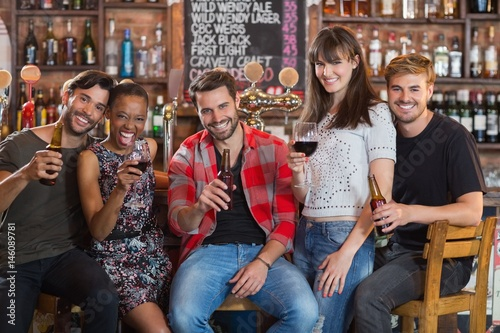 Photo  Portrait of friends holding beer bottles and wineglasses
