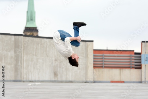 Young boy jumping somersault on the street.