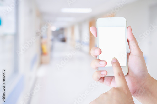 Plakat Żeńskiego ręki mienia mobilny mądrze telefon z zamazanym szpitalnym tłem