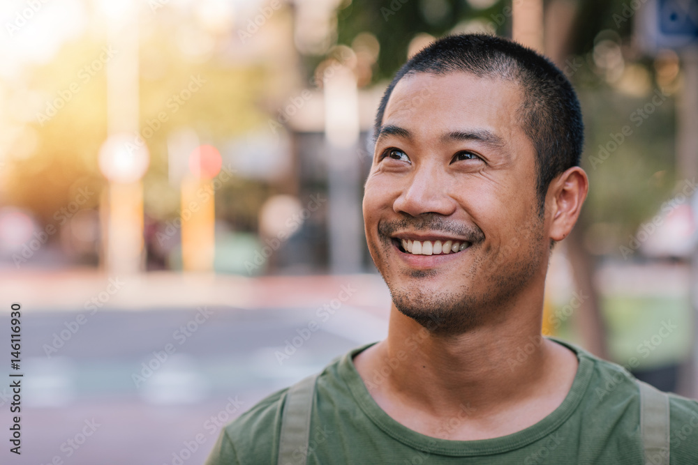 Fototapety, obrazy: Handsome young Asian man standing on a city street smiling