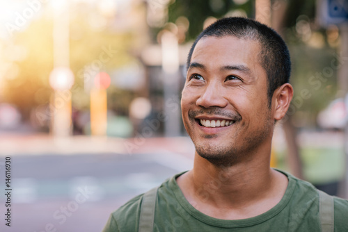 Fotografie, Obraz  Handsome young Asian man standing on a city street smiling