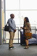 Man and woman carrying briefcases talking in lobby