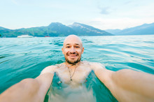 Selfie Of A Bald Happy Smiling Naked European Man Swimming In Spitz Lake In Switzerland In Cold Aquamarine Colored Water In Autumn With Mountains And Blue Sky On Background. Vacation, Travel, Hoildays