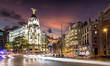 Madrid am Abend: Die beleuchtete Einkaufsstraße Gran Via mit Verkehr