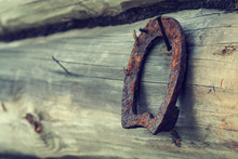 An Old Rusty Horseshoe On An Ancient Wooden Board. Retro. A Symbol Of Happiness And Good Luck. Wooden Background. Empty Place For An Inscription.