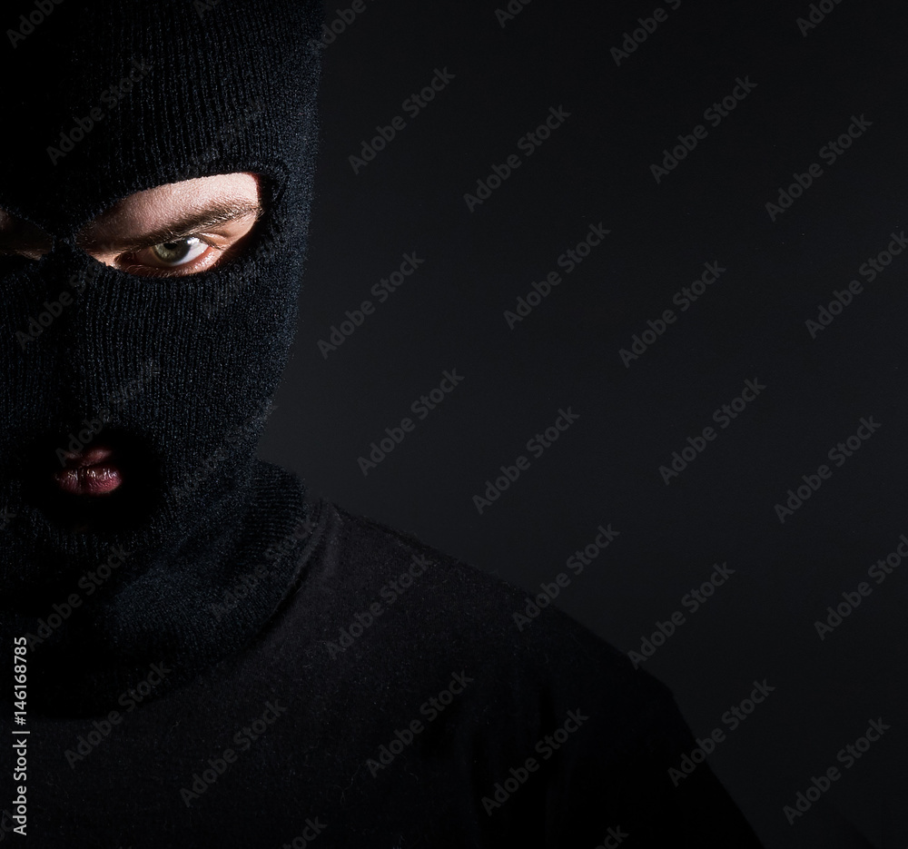 Fototapeta Man in a balaclava portrait, a thief on a dark background