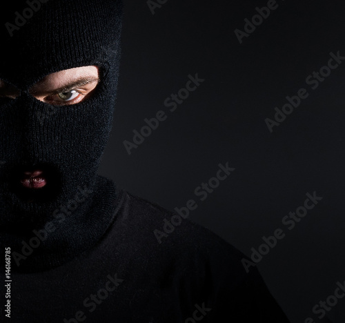 Fototapeta Man in a balaclava portrait, a thief on a dark background