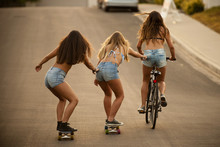 Girl Riding Bicycle Pulling Friends On Skateboard